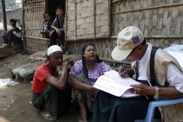 Petugas sensus Myanmar melakukan sensus terhadap permukiman keluarga Muslim Rohingya, sementara seorang polisi tampak menjaga keamanan di desa Thae Chaung, Sittwe, negara bagian Rakhine, Burma.