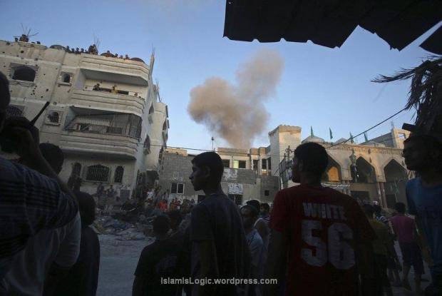 Asap mengepul dari bangunan yang menjadi sasaran serangan udara Israel, tidak jauh dari sebuah rumah yang hancur dalam serangan udara sebelumnya di Rafah di selatan Jalur Gaza, Jumat (11/7). (Reuters/Ibraheem Abu Mustafa)